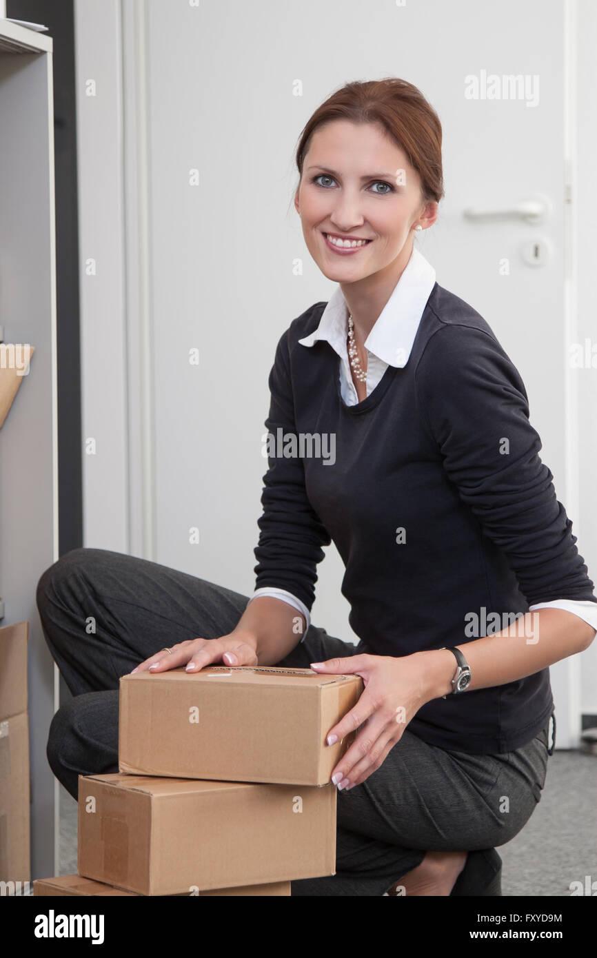 Businesswoman sortes de colis au bureau Photo Stock