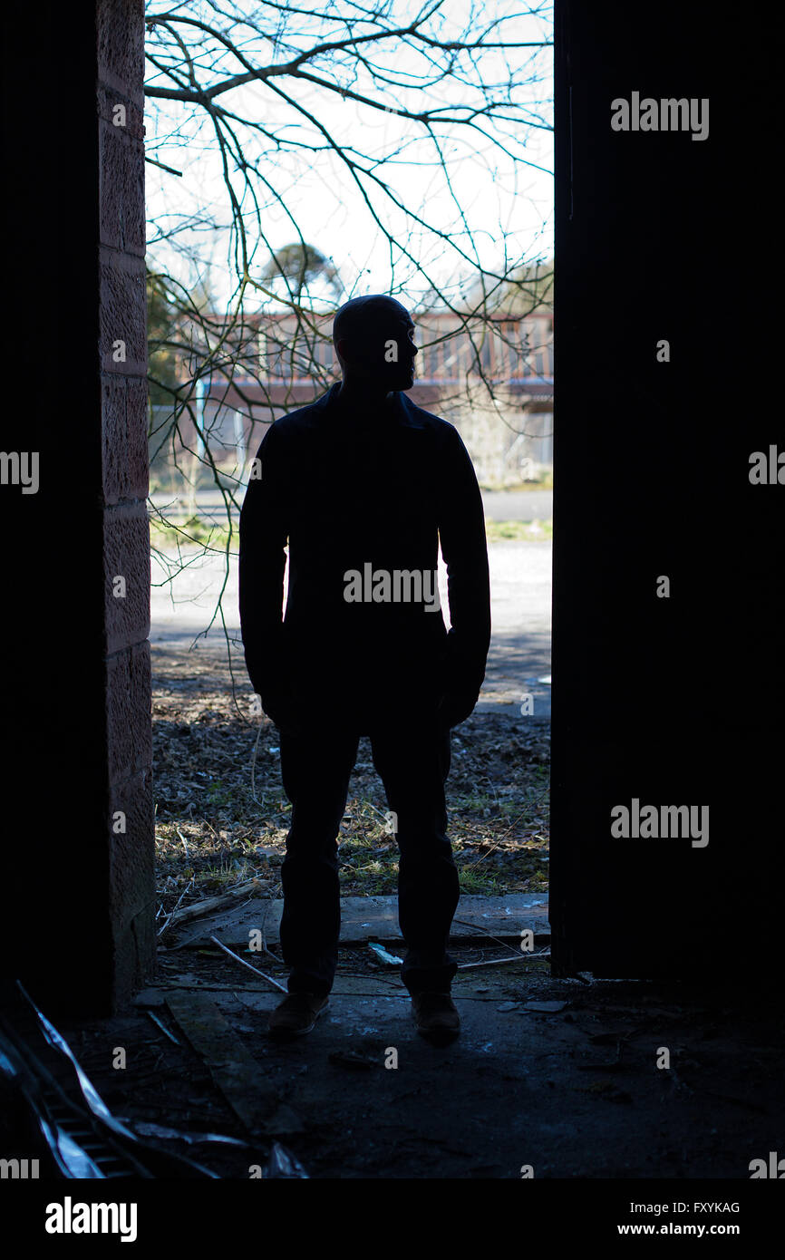 Silhouette d'un homme aux portes d'un bâtiment abandonné Photo Stock