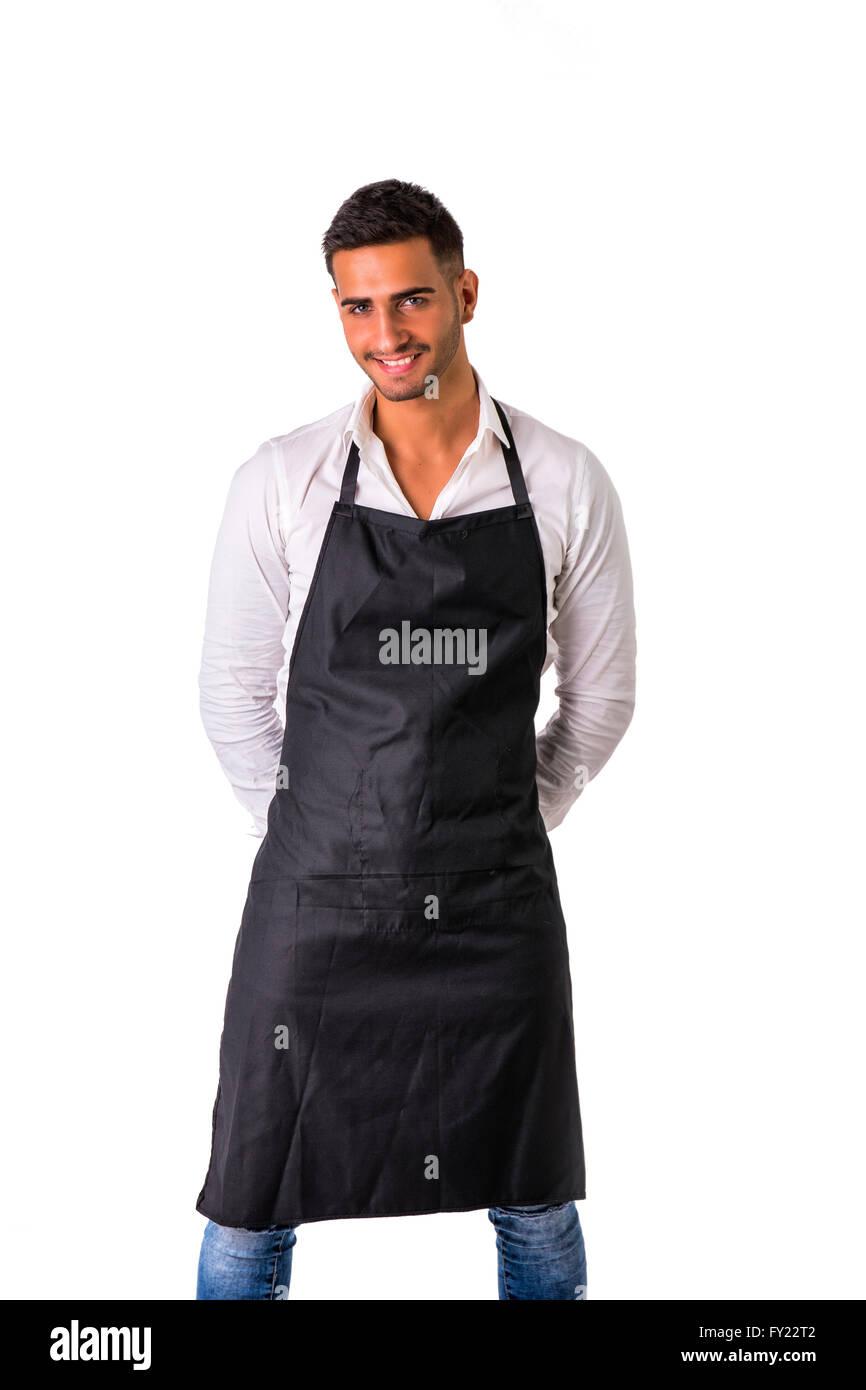 Jeune cuisinier ou serveur posant, accueille ses hôtes avec un sourire, le port de tablier noir et chemise Photo Stock
