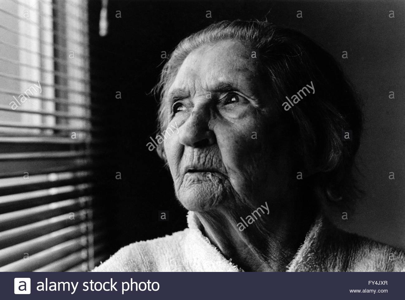 Portrait noir et blanc dune femme de 90 ans dun éclairage naturel éclairées en regardant vers la fenêtre avec store vénitien indyfoto