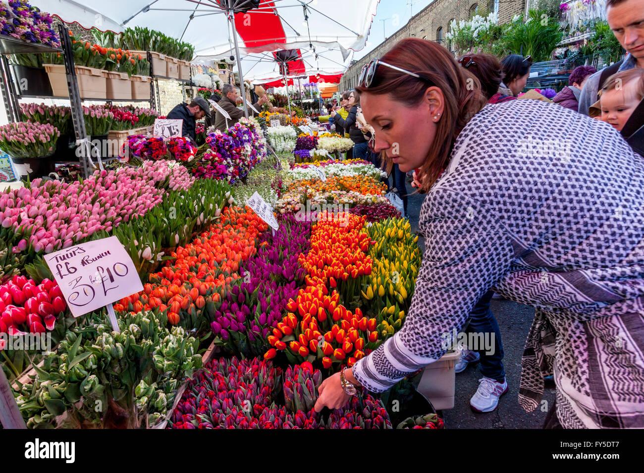 Une femme d'acheter des fleurs sur Columbia Road Flower Market, Tower Hamlets, London, England Photo Stock