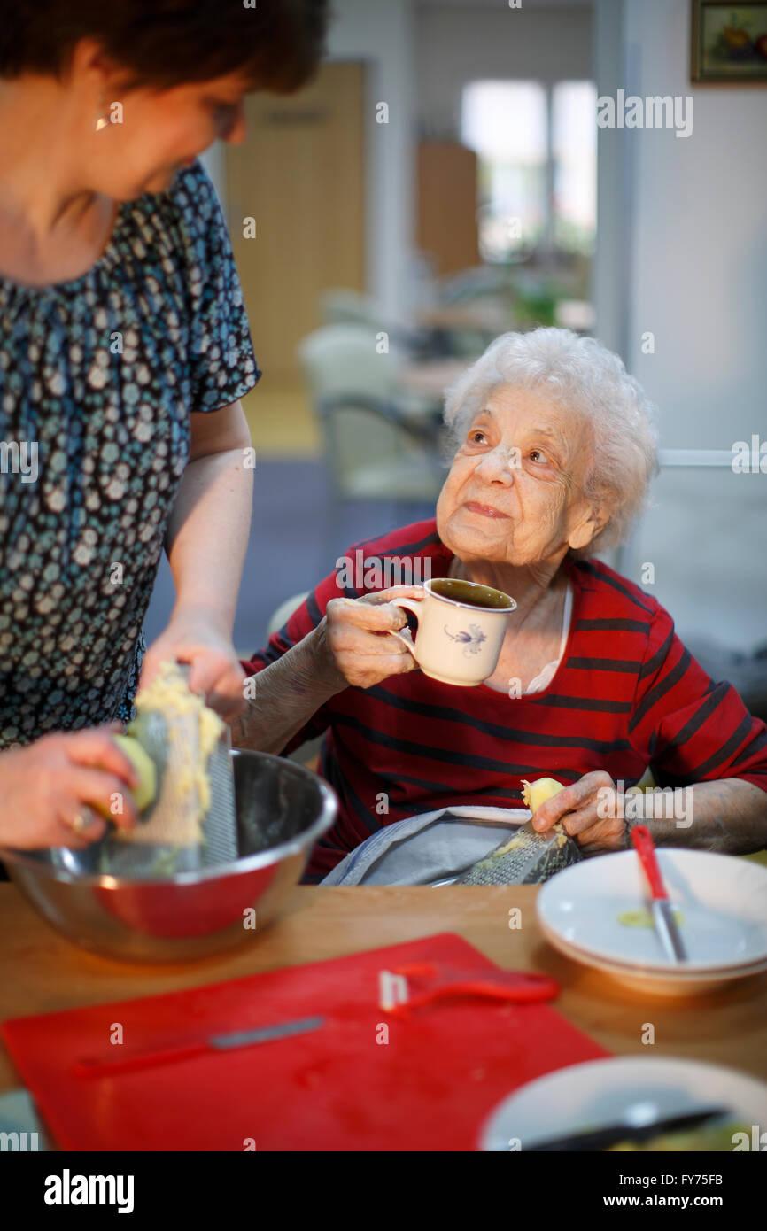 Femme, 89 ans, et d'un travailleur social, 31 ans, la cuisine comme un passe-temps pour les personnes âgées, Photo Stock
