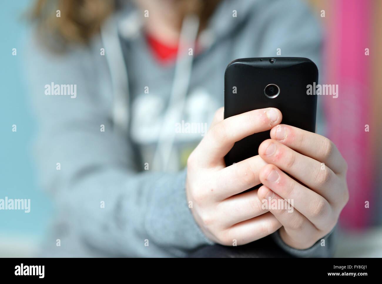 Teen holding mobile (cellulaire) téléphone en mains Photo Stock