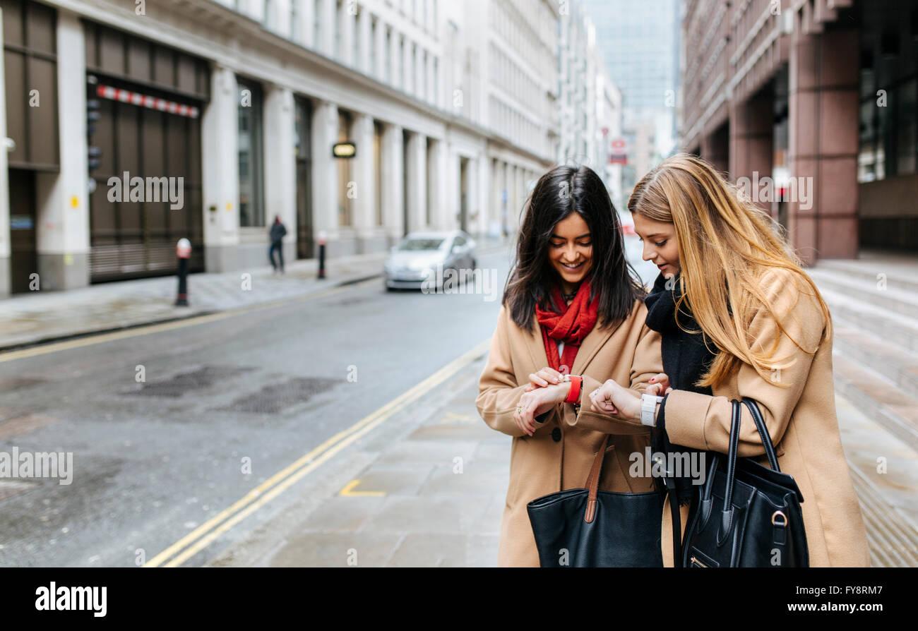 UK, Londres, deux amis à la découverte de la ville, contrôle de montres intelligentes Photo Stock