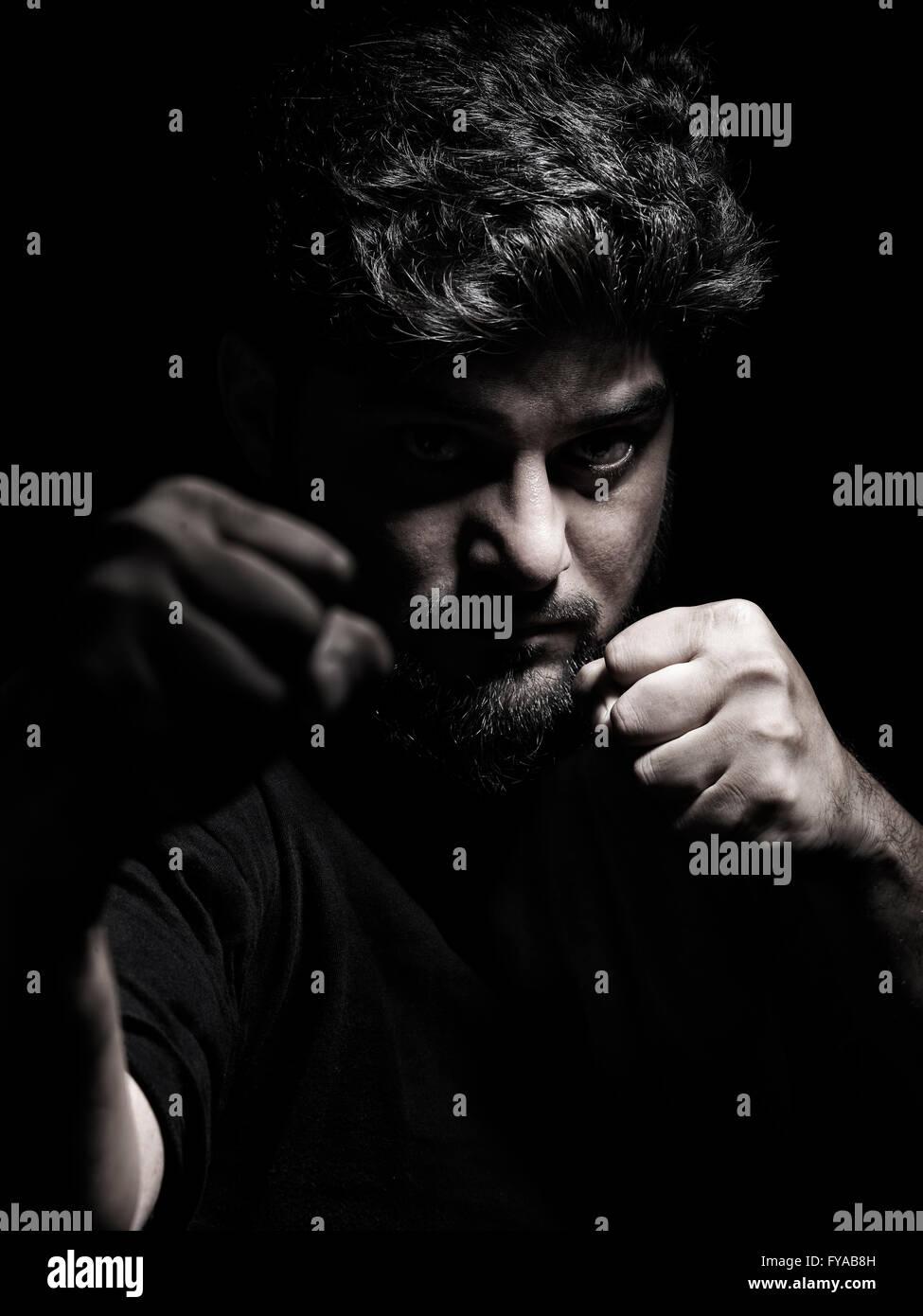 Portrait dramatique d'un homme dans une position de combat avec les poings devant son visage Photo Stock