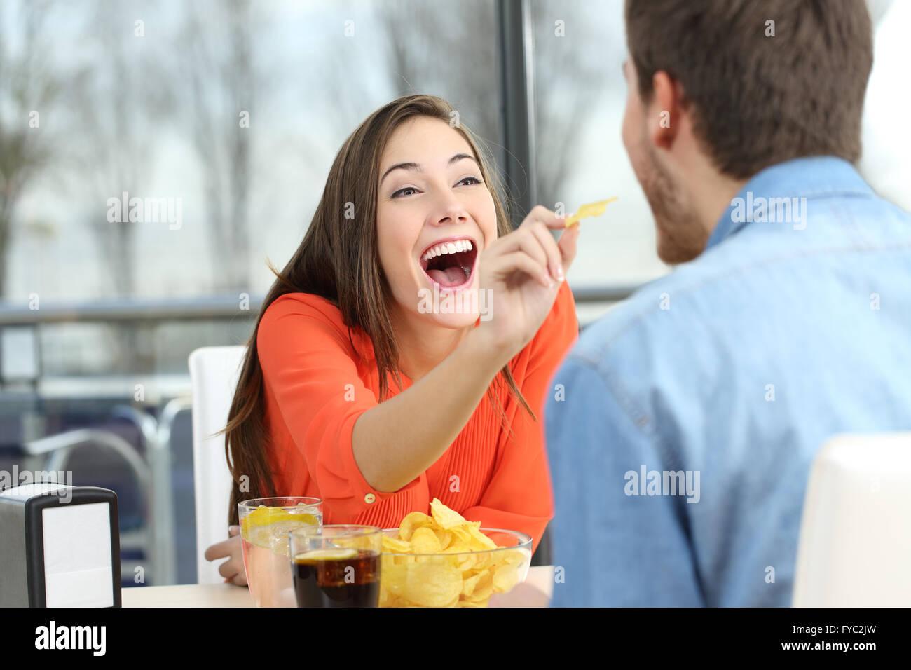 Playful couple puce manger des pommes de terre et de plaisanter à l'autre dans une date dans un café Photo Stock