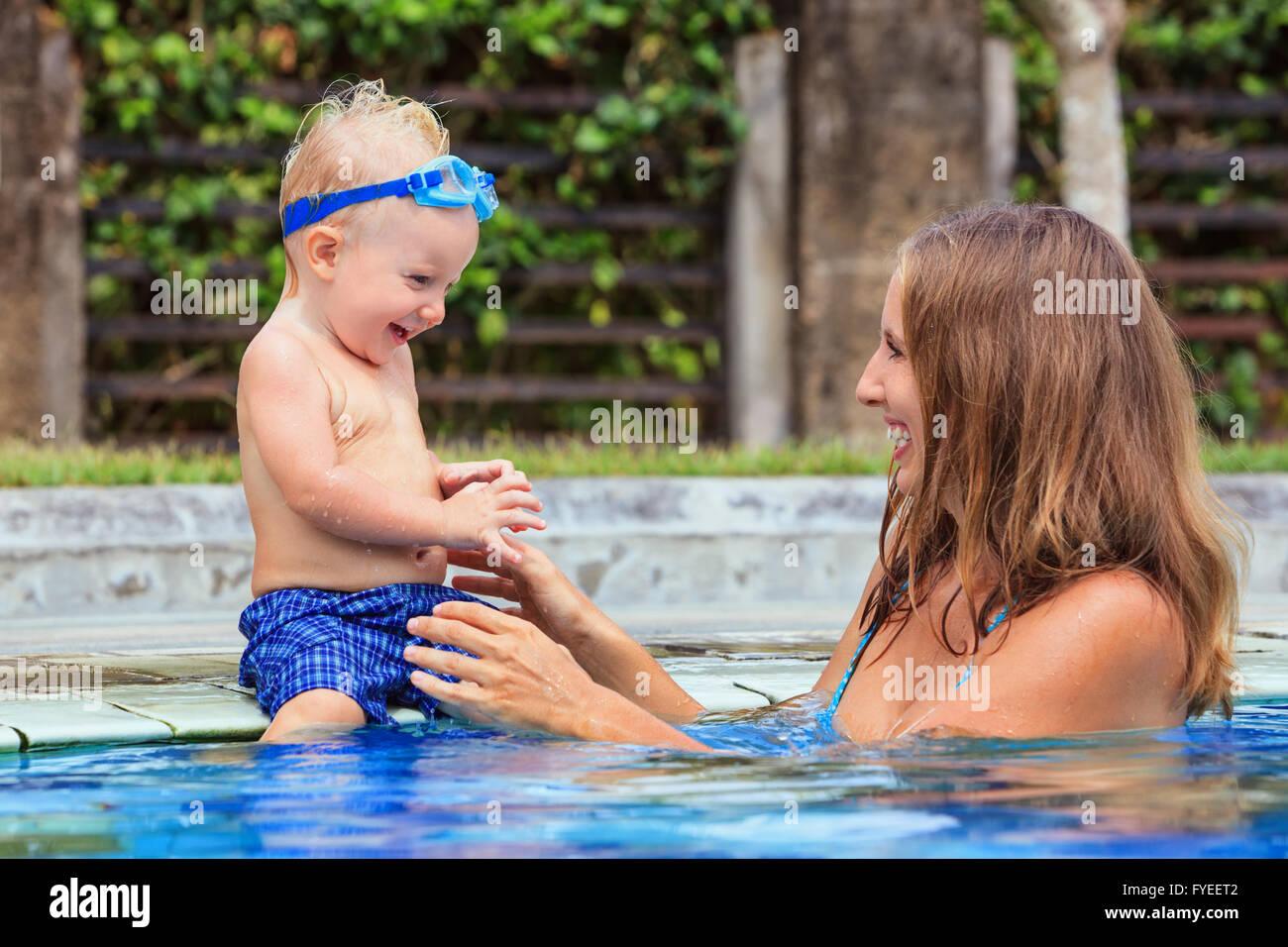 Peu de natation enfant à lunettes sous-marines s'asseoir sur le bord de la piscine a fun - jouer avec bébé Photo Stock