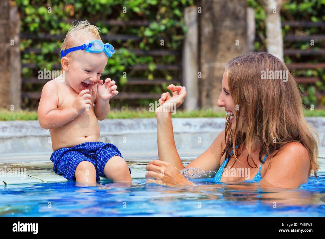 Peu de natation enfant à lunettes sous-marines s'asseoir sur le bord de la piscine a l'amusement - Photo Stock