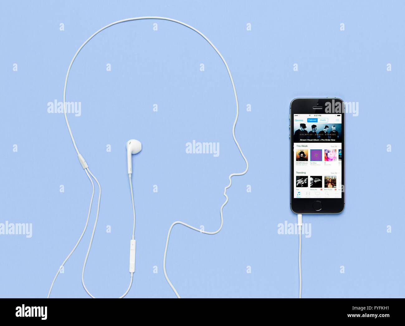 Câble du casque énoncés dans la forme de la tête d'un homme connecté à un iPhone Photo Stock