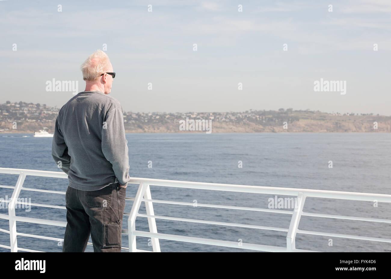 L'âge moyen homme habillé en passant le port de lunettes est à côté d'une balustrade Photo Stock