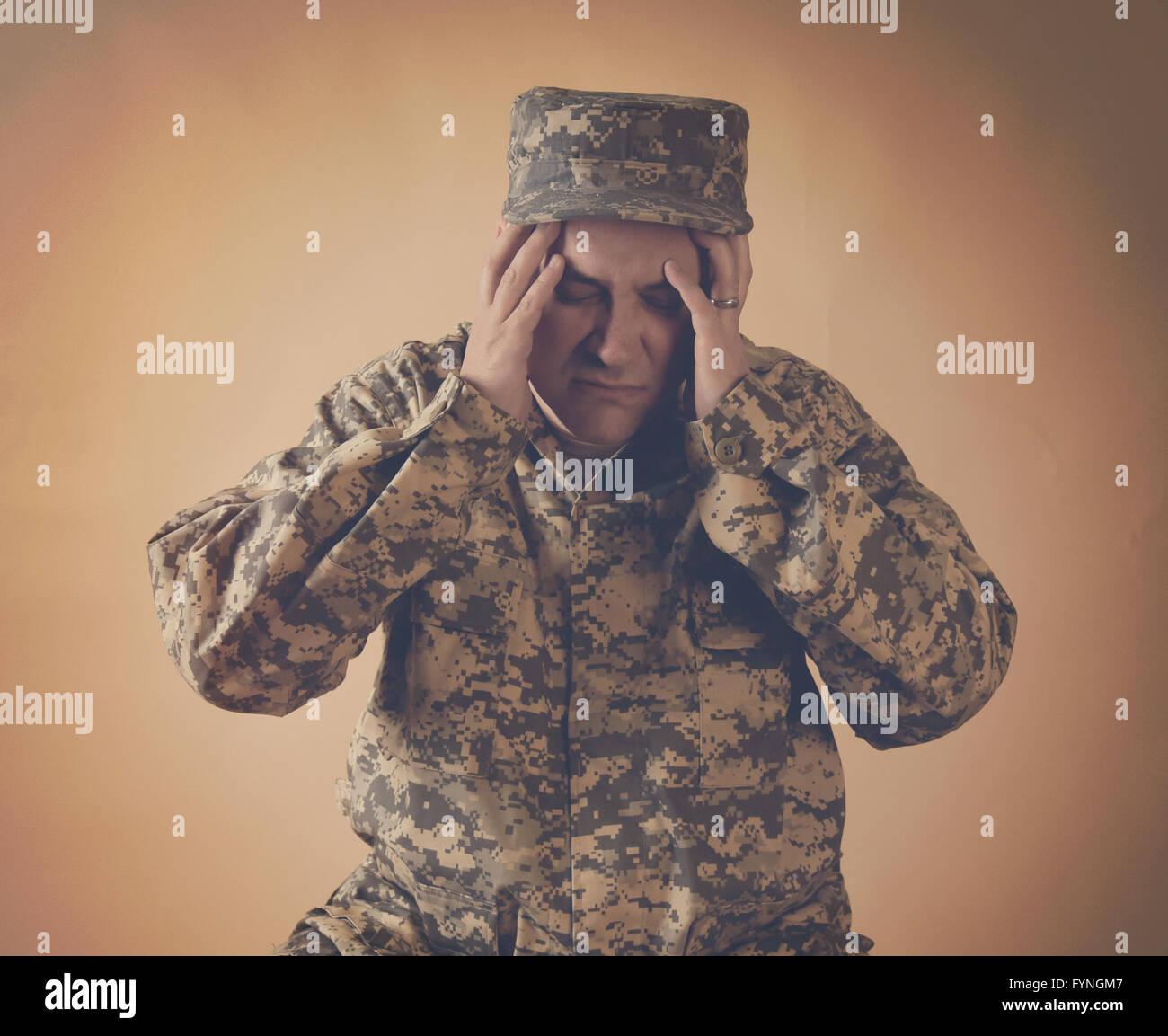 Un homme de l'armée a souligné tient ses mains à sa tête sur un arrière-plan pour un Photo Stock