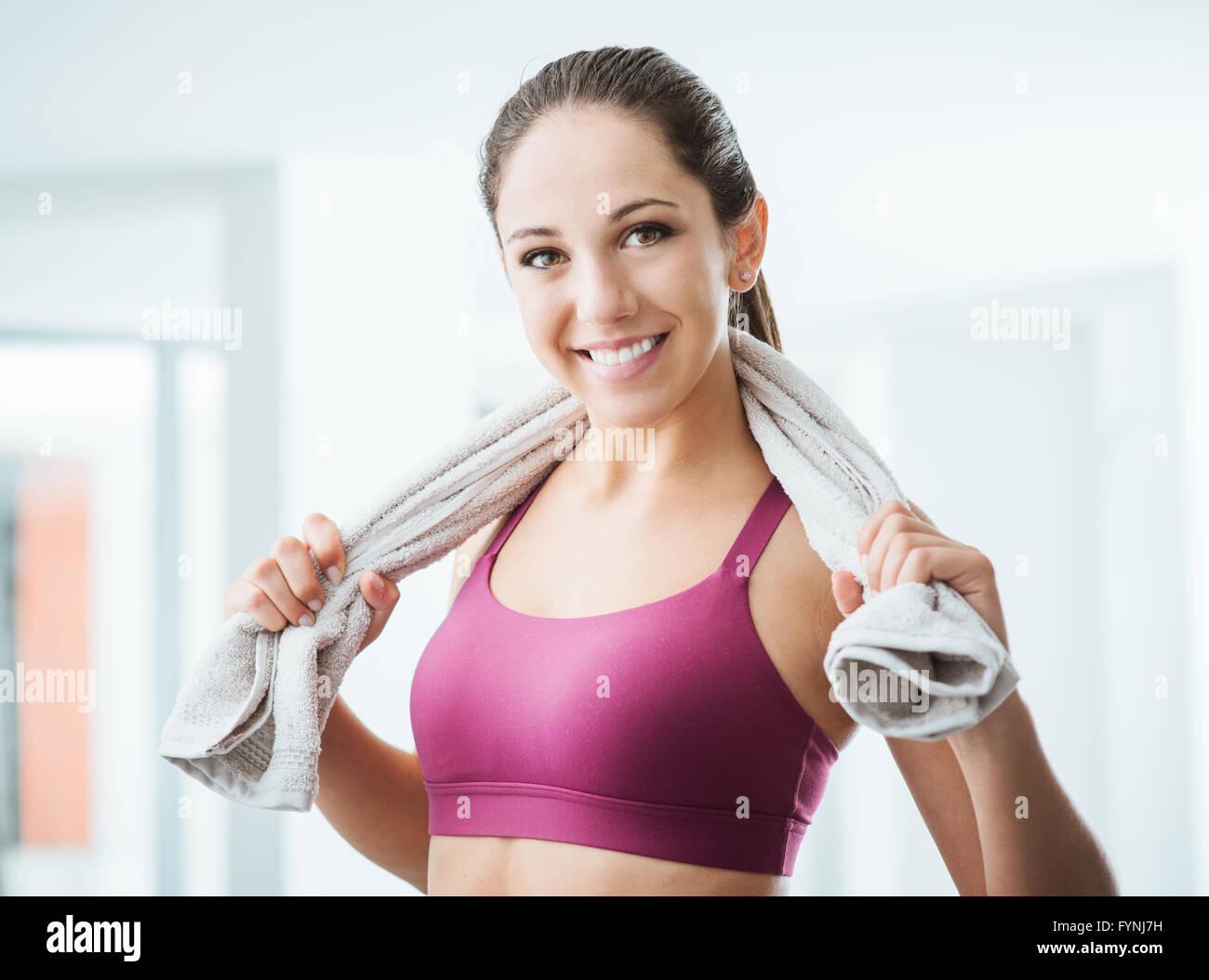 Belle femme sportive avec sèche-serviettes dans la salle de sport de détente après l'entraînement, le mode de vie sain et fitness concept Banque D'Images