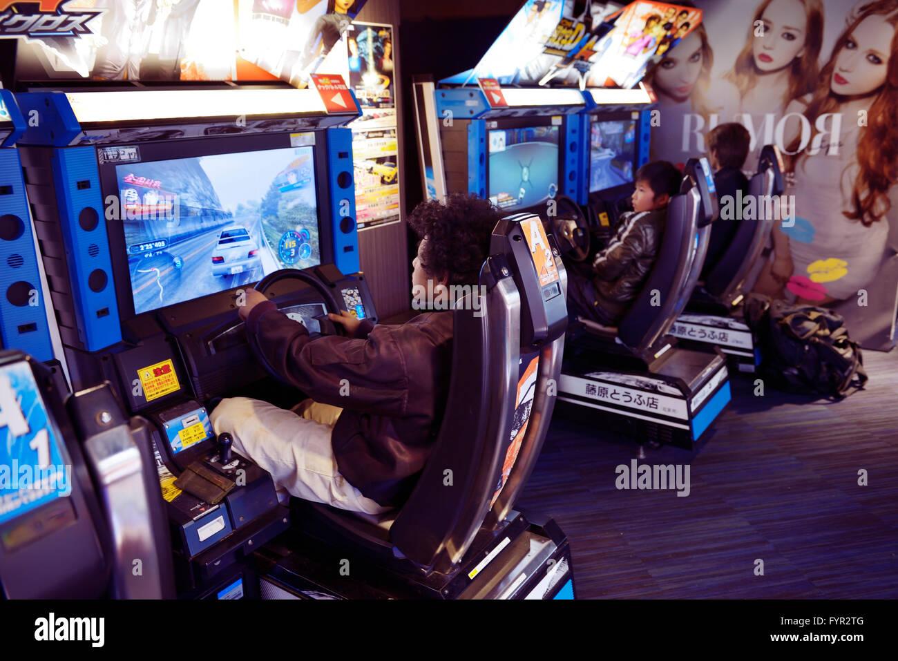 Gens jouer jeu vidéo de machines à sous dans une arcade, Tokyo, Japon Photo Stock