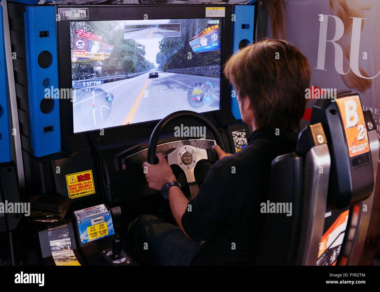Personne jouant jeu vidéo de machine à sous une arcade, Tokyo, Japon Photo Stock