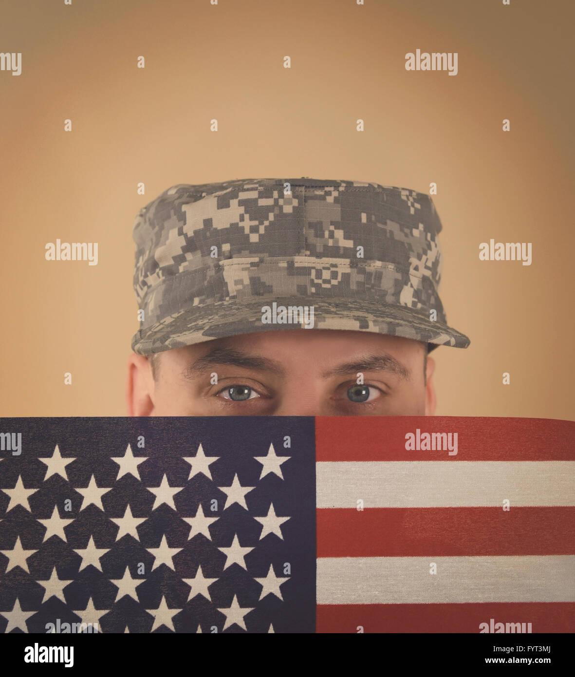Un soldat de l'armée militaire est maintenant un drapeau américain jusqu'à son visage avec Photo Stock