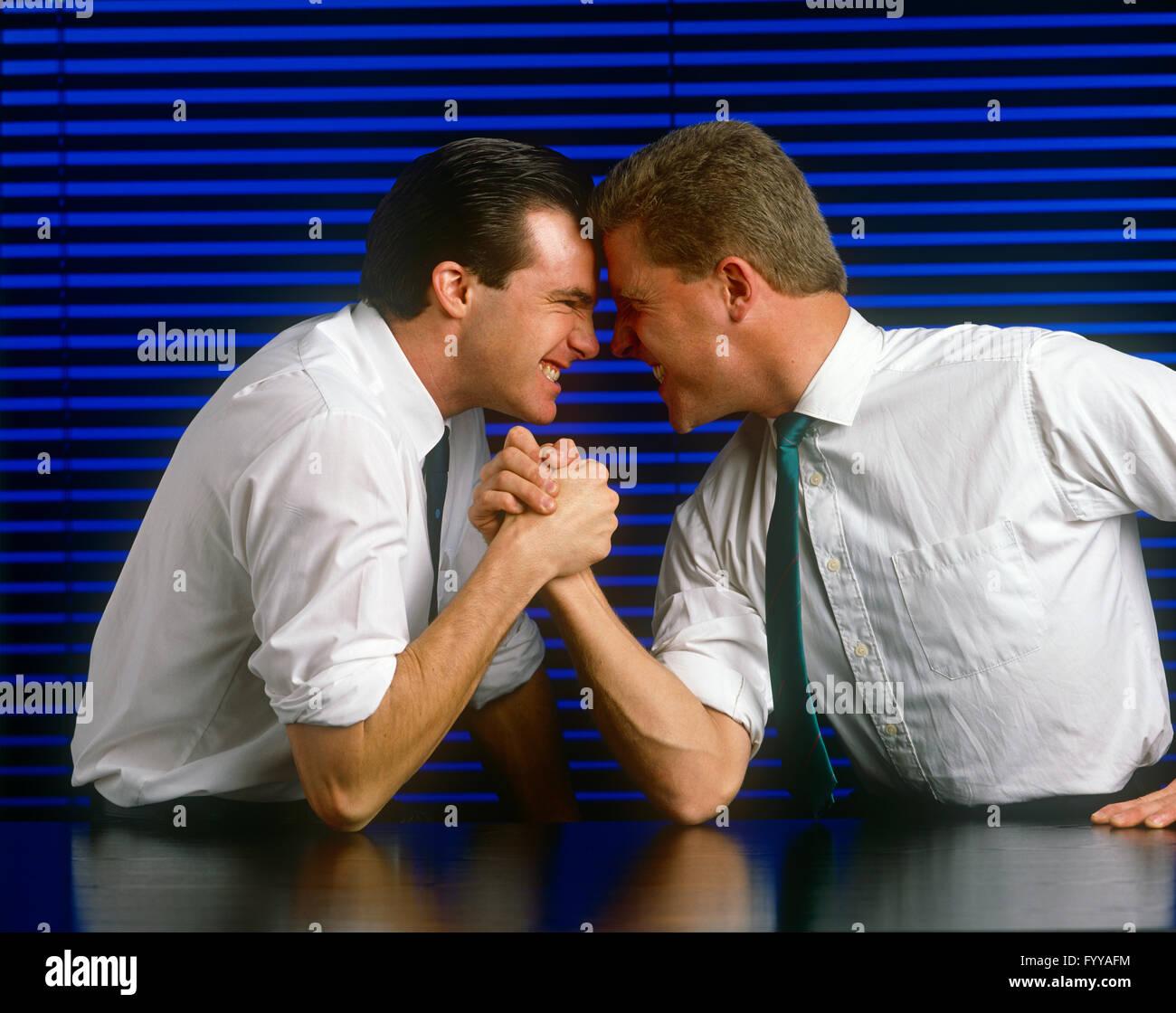 Deux mecs en vêtements intelligents ayant un avantage concurrentiel à l'intérieur, bras de fer. Photo Stock