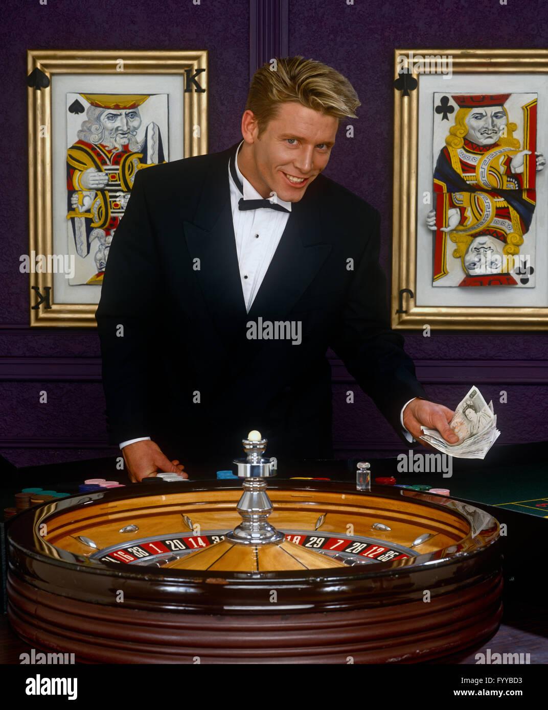 Concessionnaire mâle dans un casino par une roue de roulette, à l'intérieur. Photo Stock
