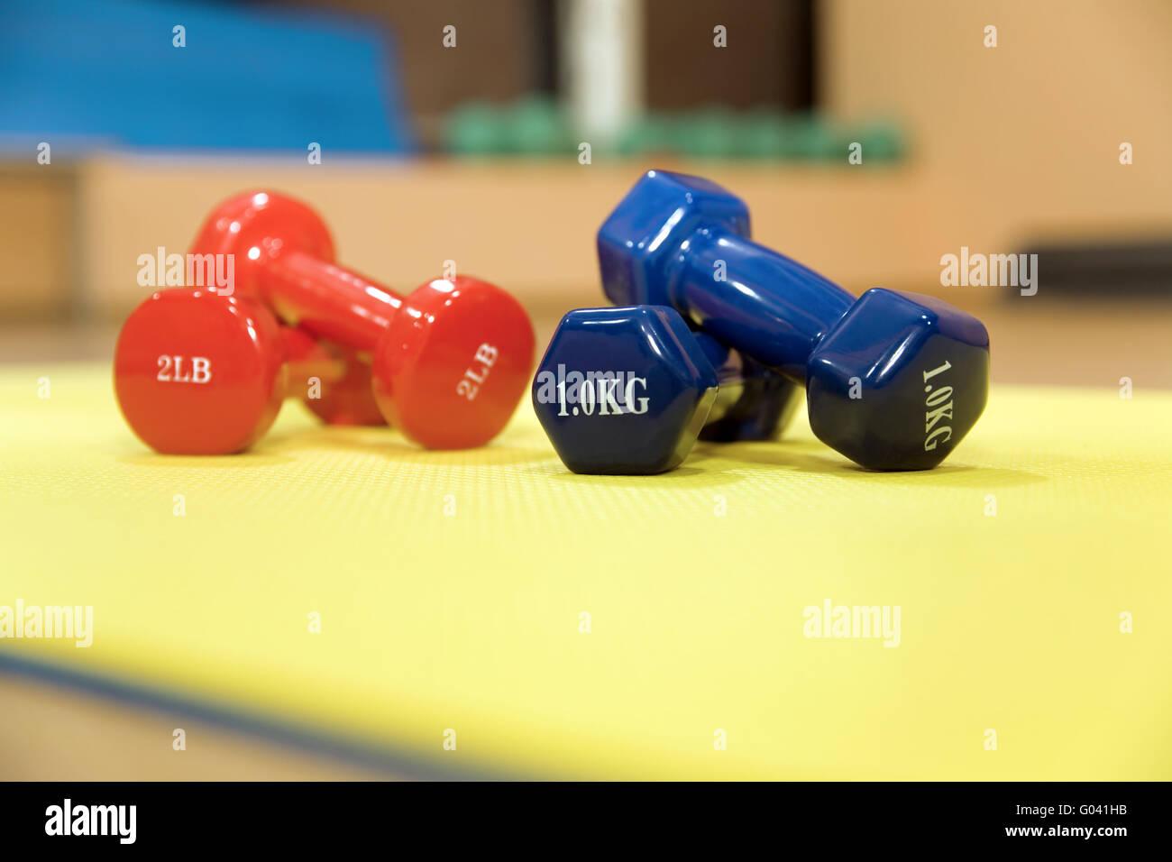 Le rouge et le bleu les haltères dans un hall moderne pour le sport Photo Stock