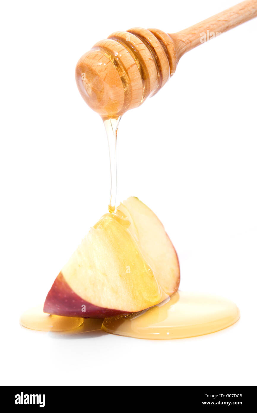 Stick avec des gouttes de miel sur pomme rouge isolé sur fond blanc Photo Stock