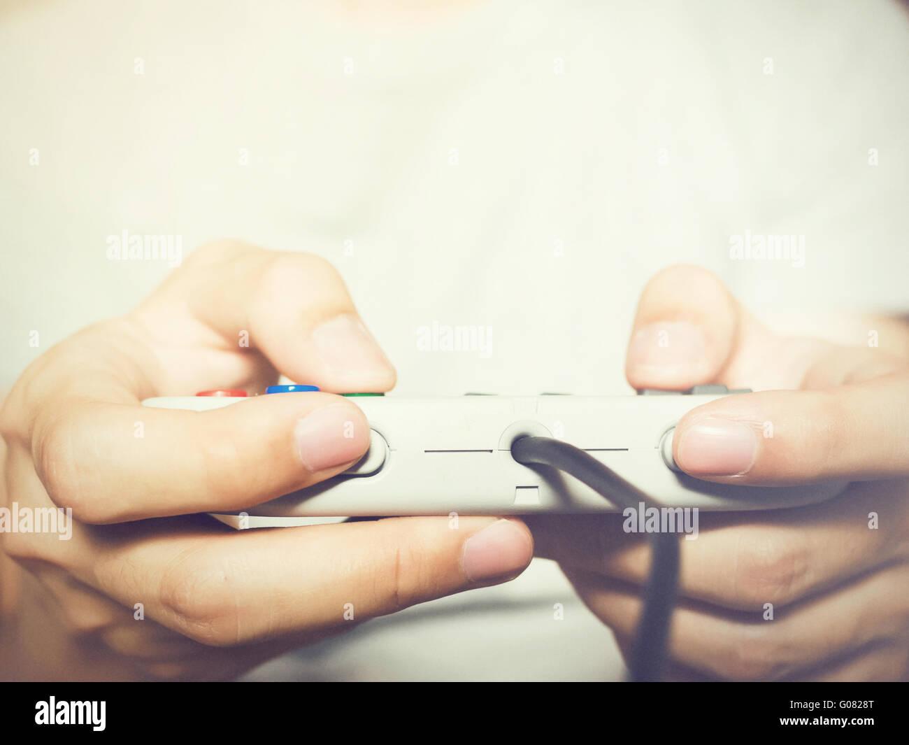 Un jeune homme tenant un contrôleur de jeu à jouer à des jeux vidéo (vintage) Photo Stock