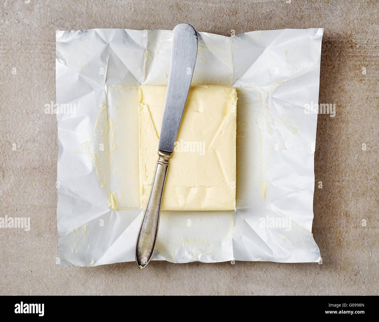 Paquet de beurre à l'aide d'un couteau, vue du dessus Photo Stock