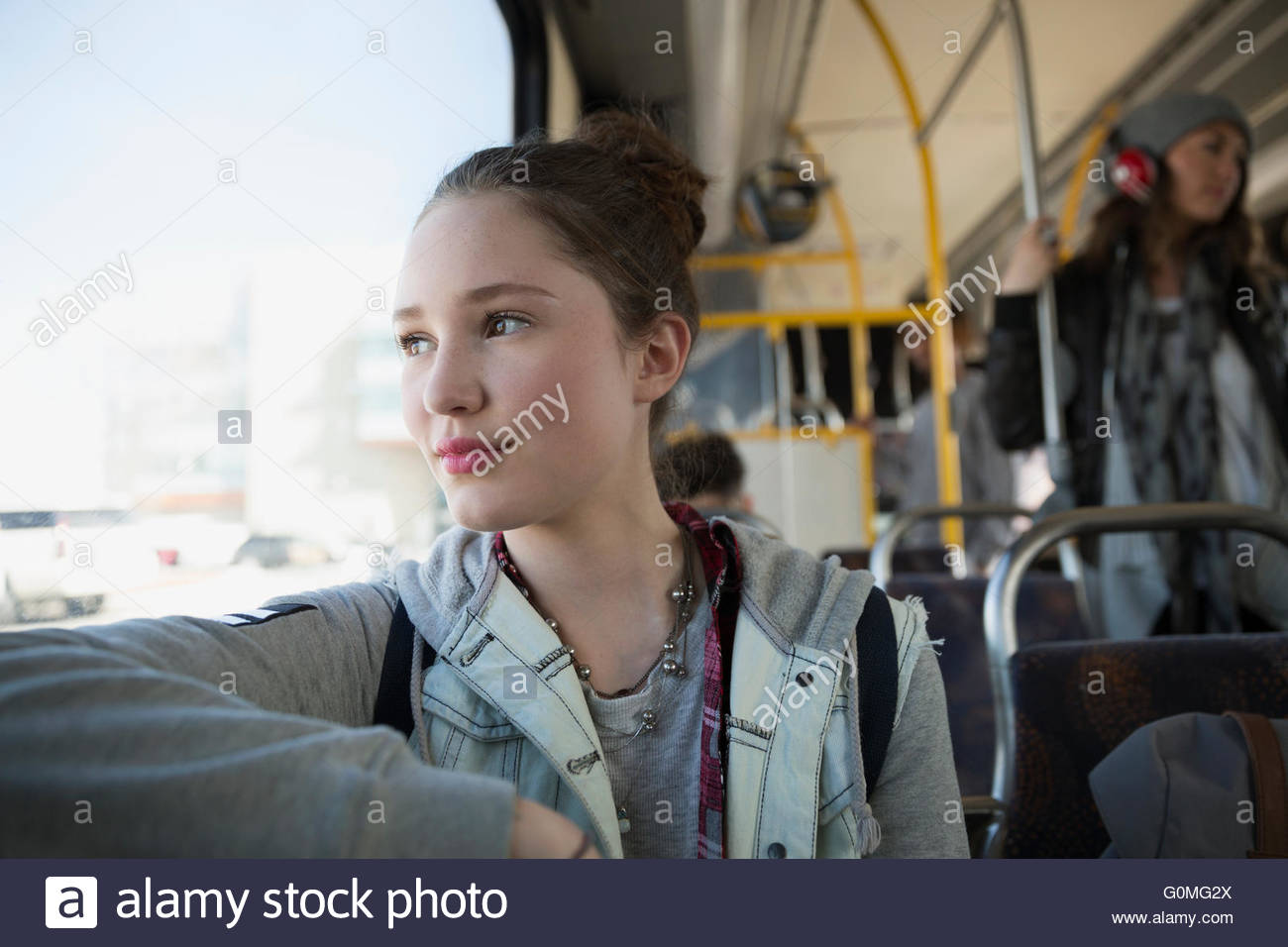 Pensive teenage girl riding bus looking out window Photo Stock