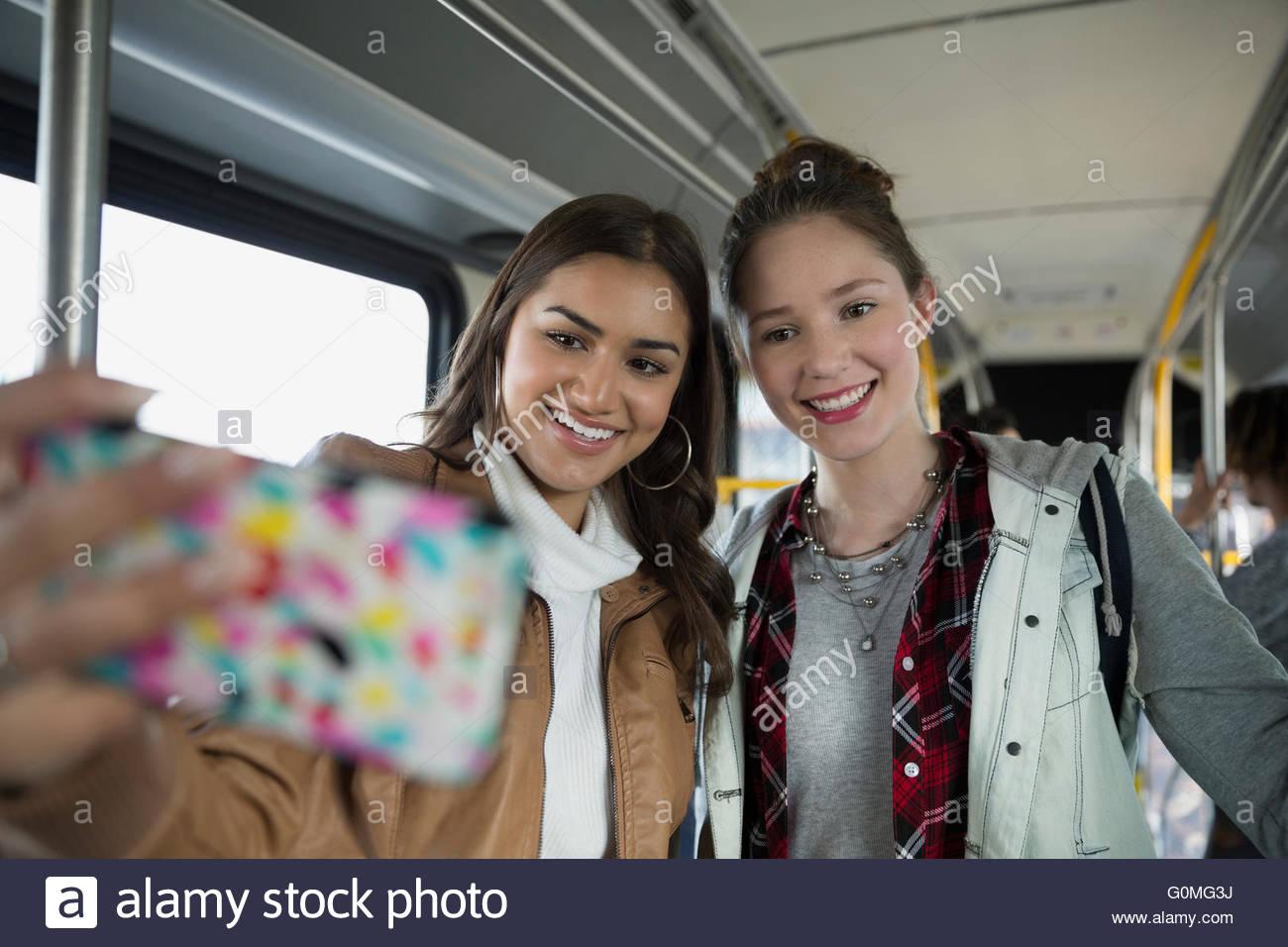 Les adolescentes en tenant un téléphone cellulaire selfies sur bus Photo Stock
