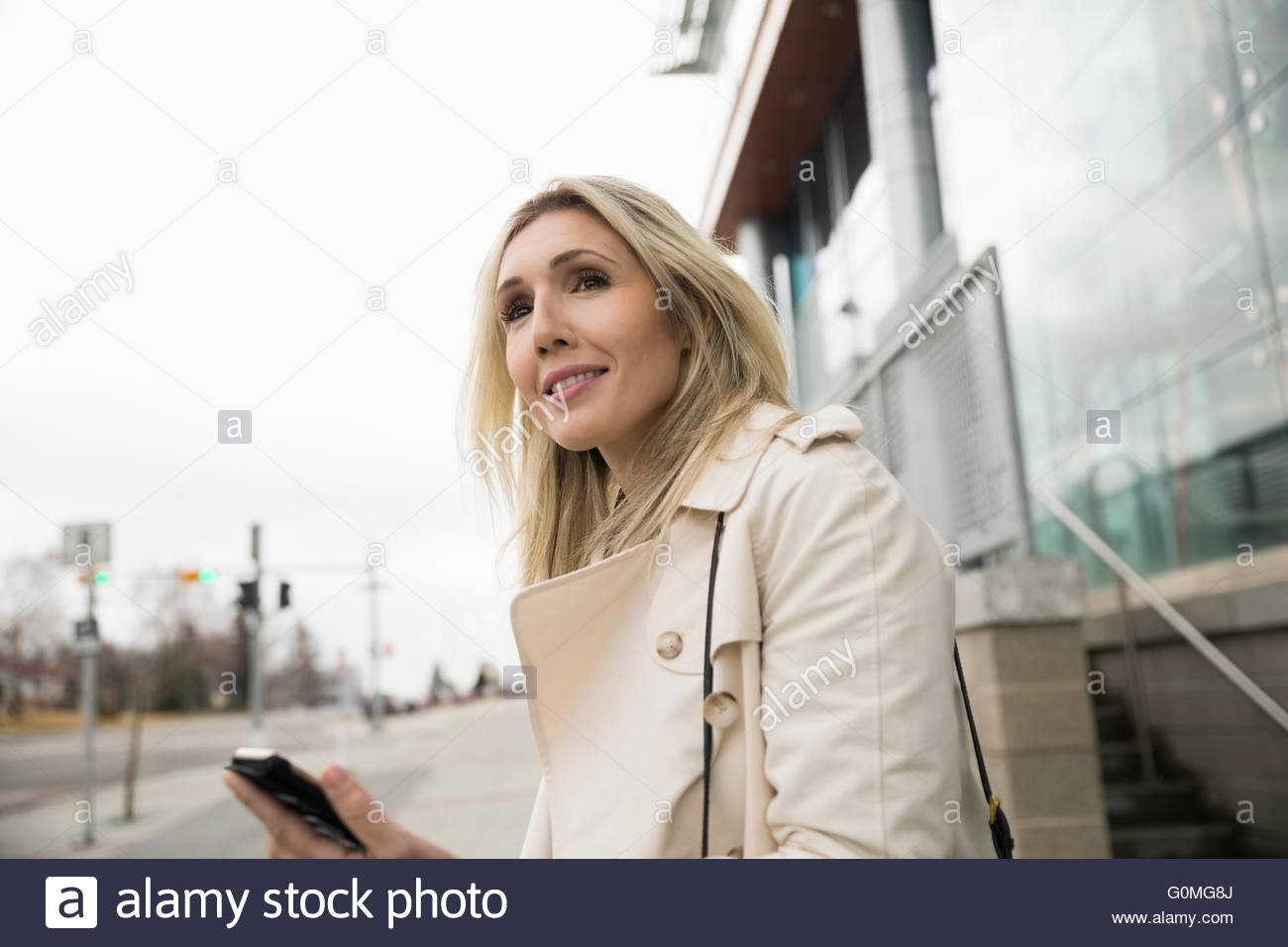 Businesswoman with cell phone en attente de taxi Photo Stock