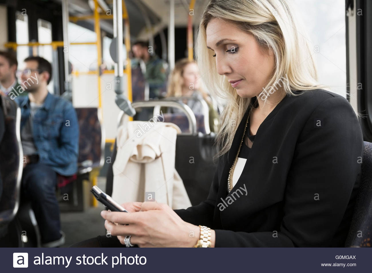 Businesswoman texting with cell phone on bus Photo Stock