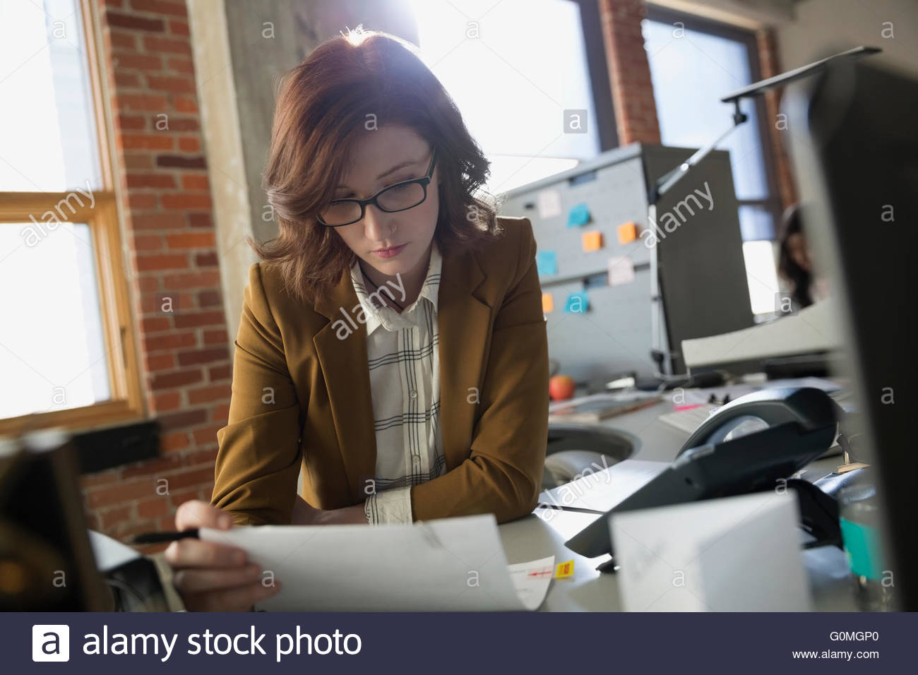L'accent businesswoman reading paperwork at office desk Photo Stock
