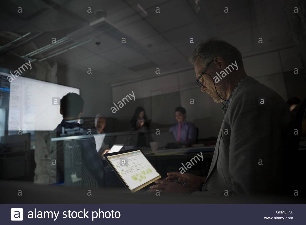 Ordinateur portable à l'aide d'architecte réunion salle de conférence sombre Photo Stock