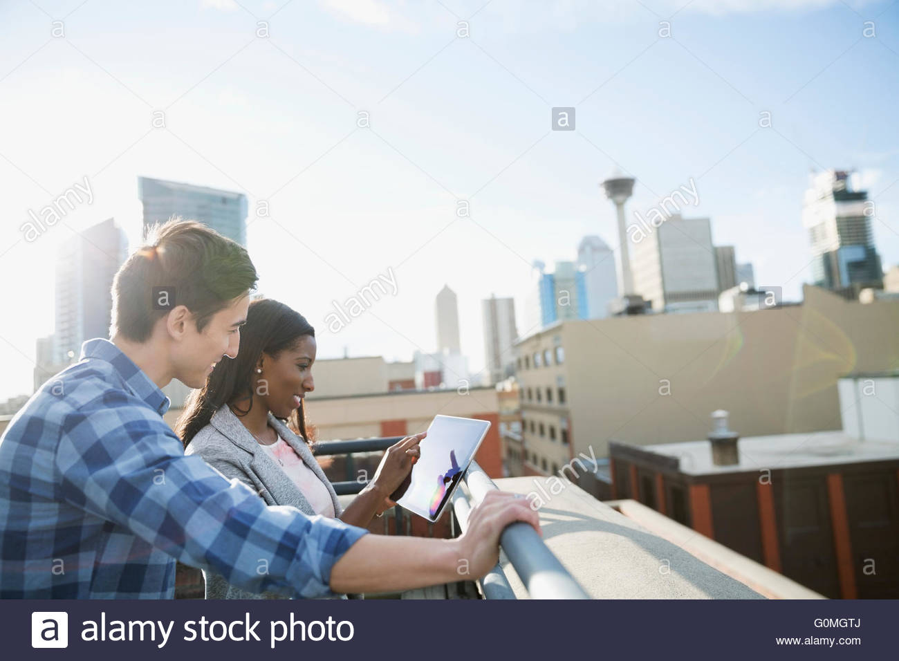 Businessman and businesswoman using digital tablet urban rooftop Photo Stock