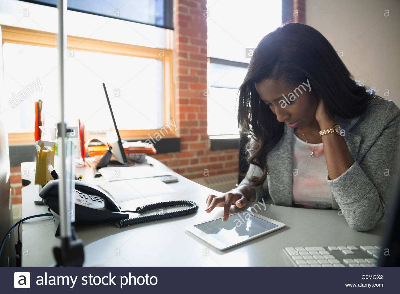 Businesswoman using digital tablet at office desk Photo Stock