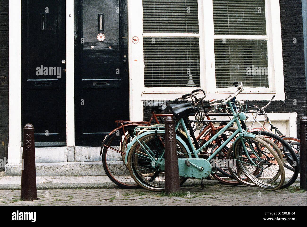 Un tas de bicyclettes debout appuyée contre un trottoir bollard. Photo Stock