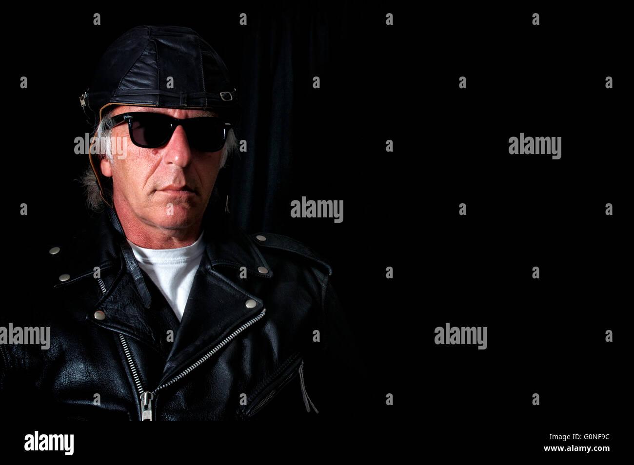 d5378aa432f9f5 Une ancienne école biker veste en cuir vintage port de lunettes rétro, cuir  et casque aviateur à de graves contre l arrière-plan noir, copiez l espace.