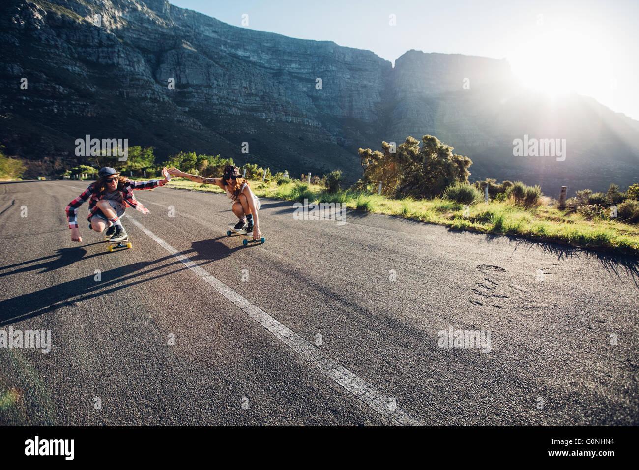Jeune couple patinage de sur la route. Jeune homme et femme s'amuser tout en patinant ensemble sur une journée Photo Stock