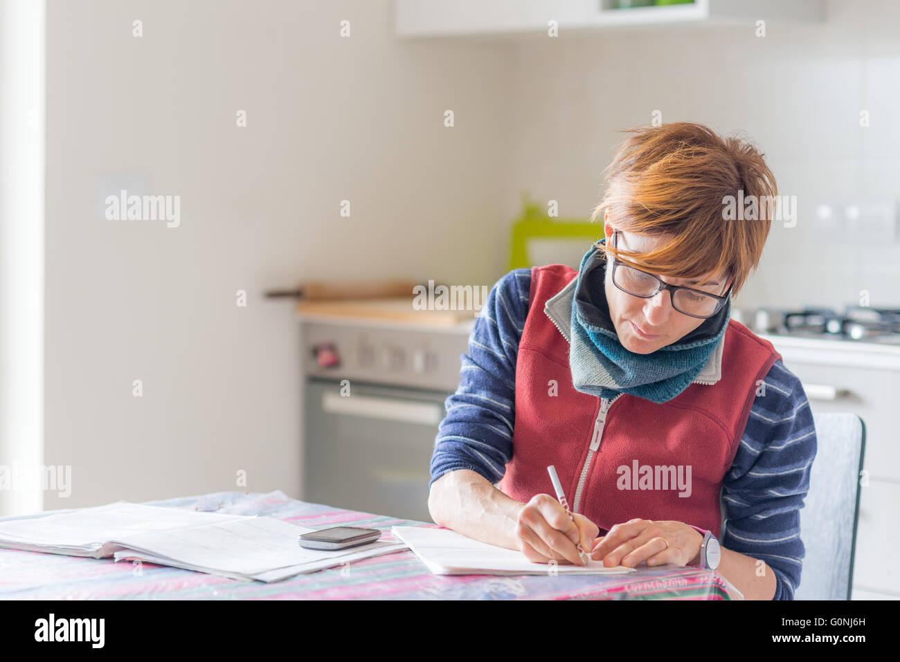 Femme à lunettes assis à table, la lecture et l'écriture les formalités administratives Photo Stock