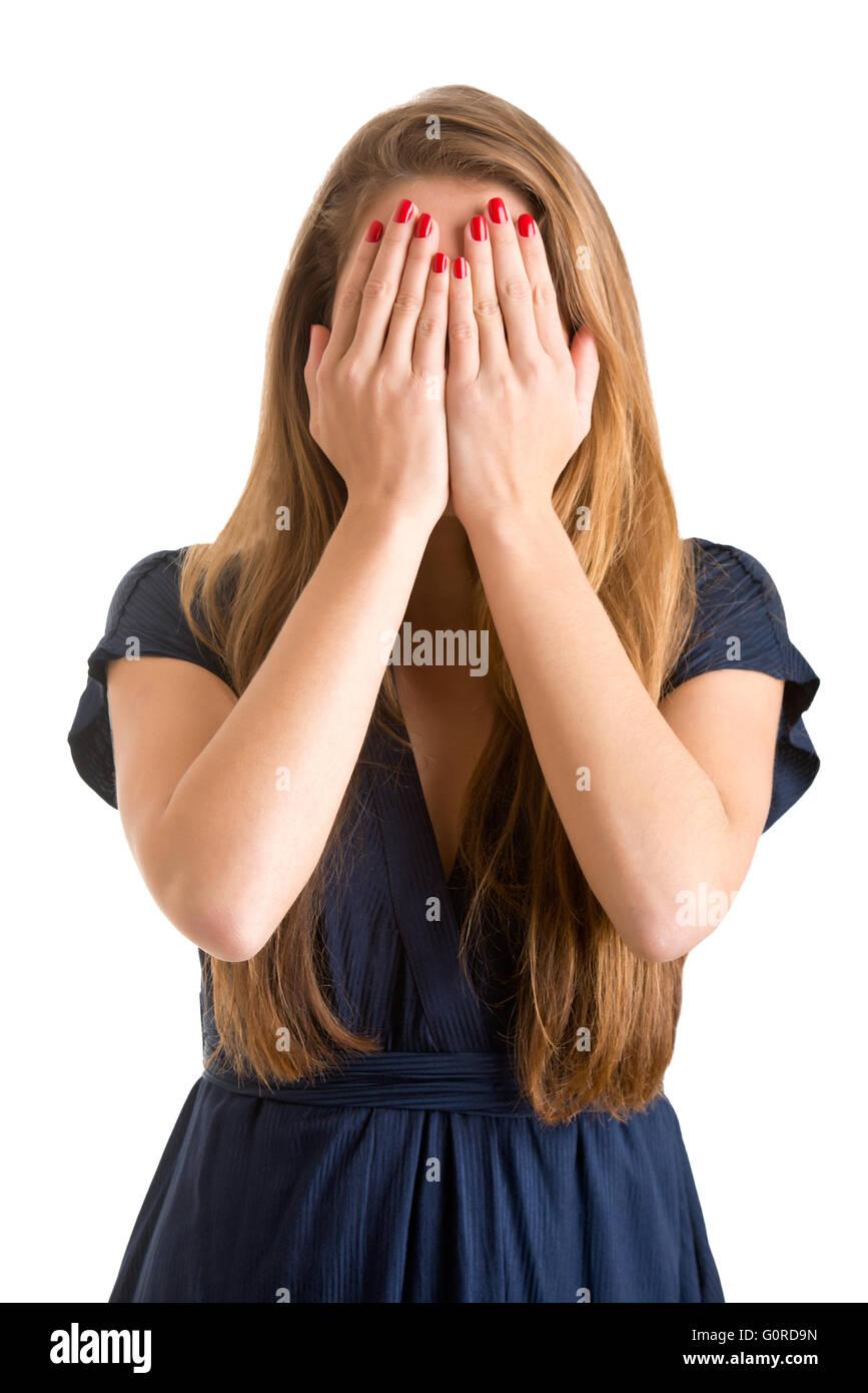 Jeune fille timide, couvrant son visage avec ses mains, isolé Photo Stock