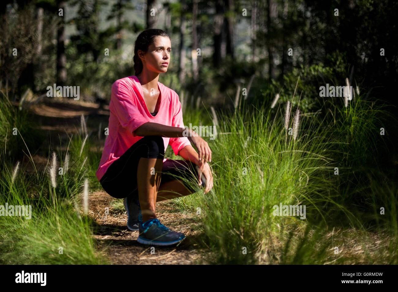 Sourire femme posant squat Photo Stock