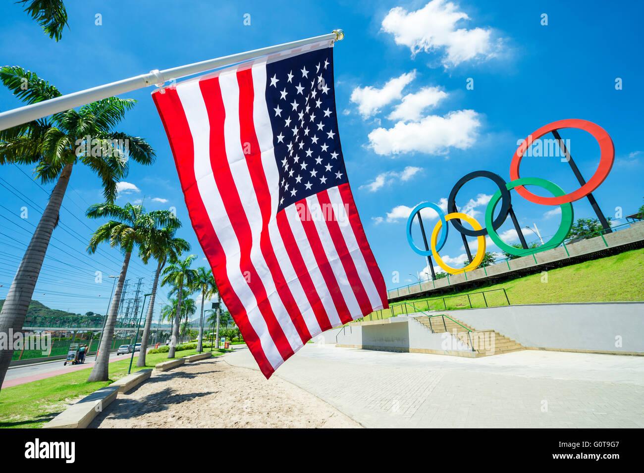 RIO DE JANEIRO - le 18 mars 2016: un drapeau américain est en face d'un affichage des anneaux olympiques Photo Stock