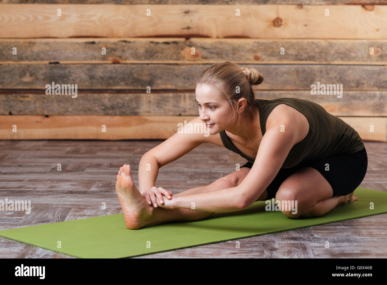 Woman doing yoga exercises on yoga mat Photo Stock