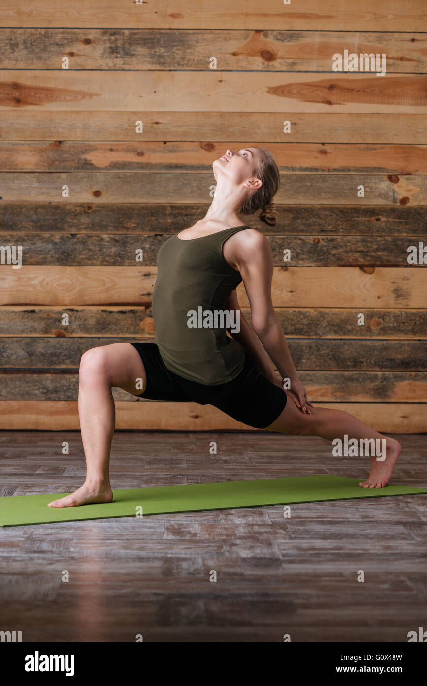 Attractive woman doing stretching exercises on yoga mat Photo Stock
