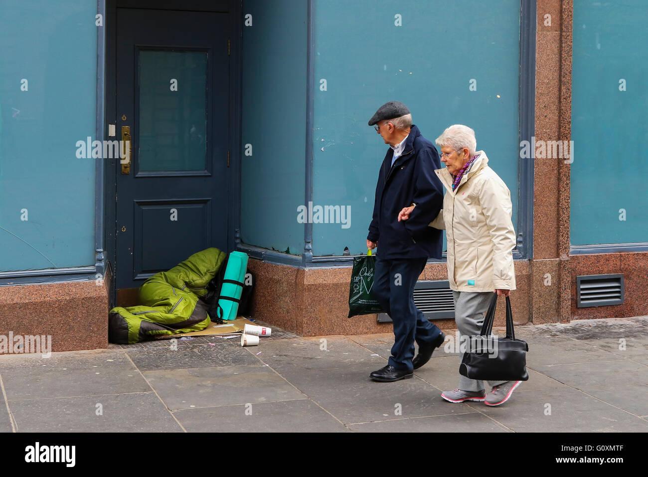 L'homme et de la femme en passant devant quelqu'un sans-abri dans un magasin porte, Glasgow, ville, Ecosse, Photo Stock