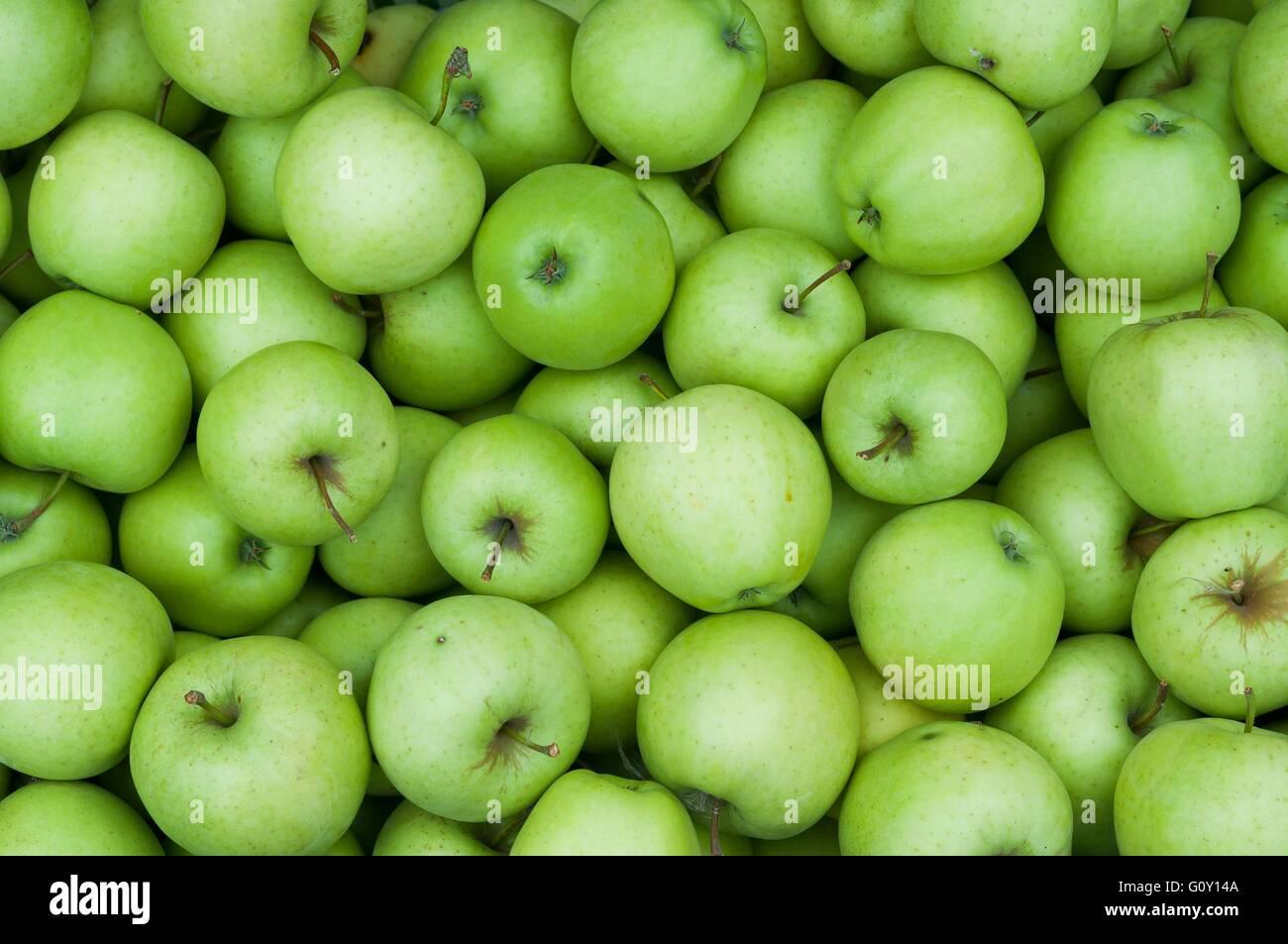 Tas de frais vert pommes Granny Smith. Image en arrière-plan Photo Stock