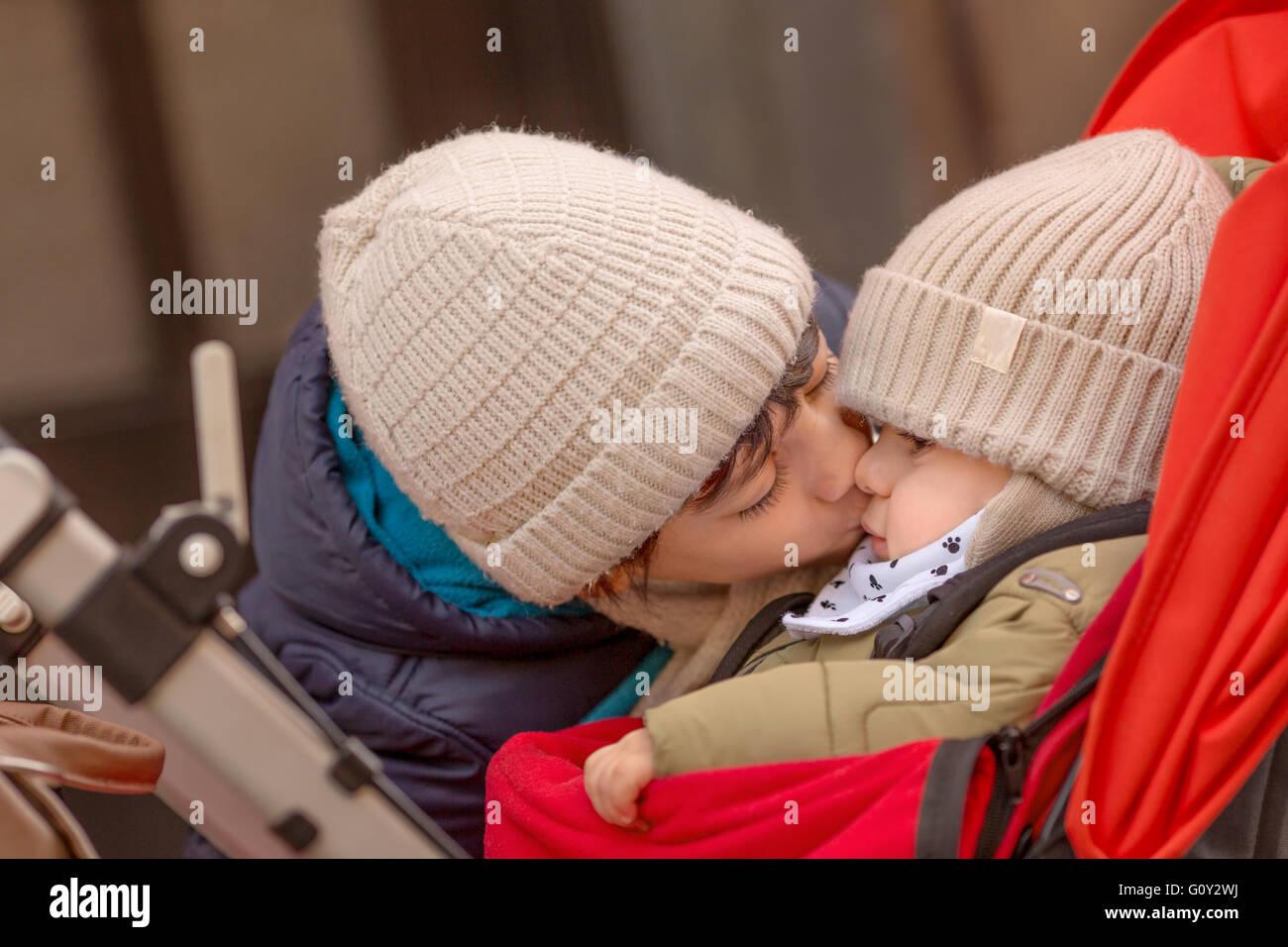 Boy kissing baby brother en poussette Banque D'Images