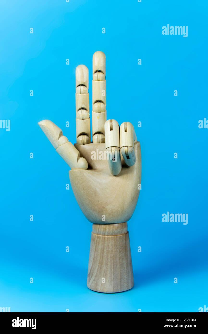 Bois à la main, main en bois, trois doigts, sur fond bleu Photo Stock