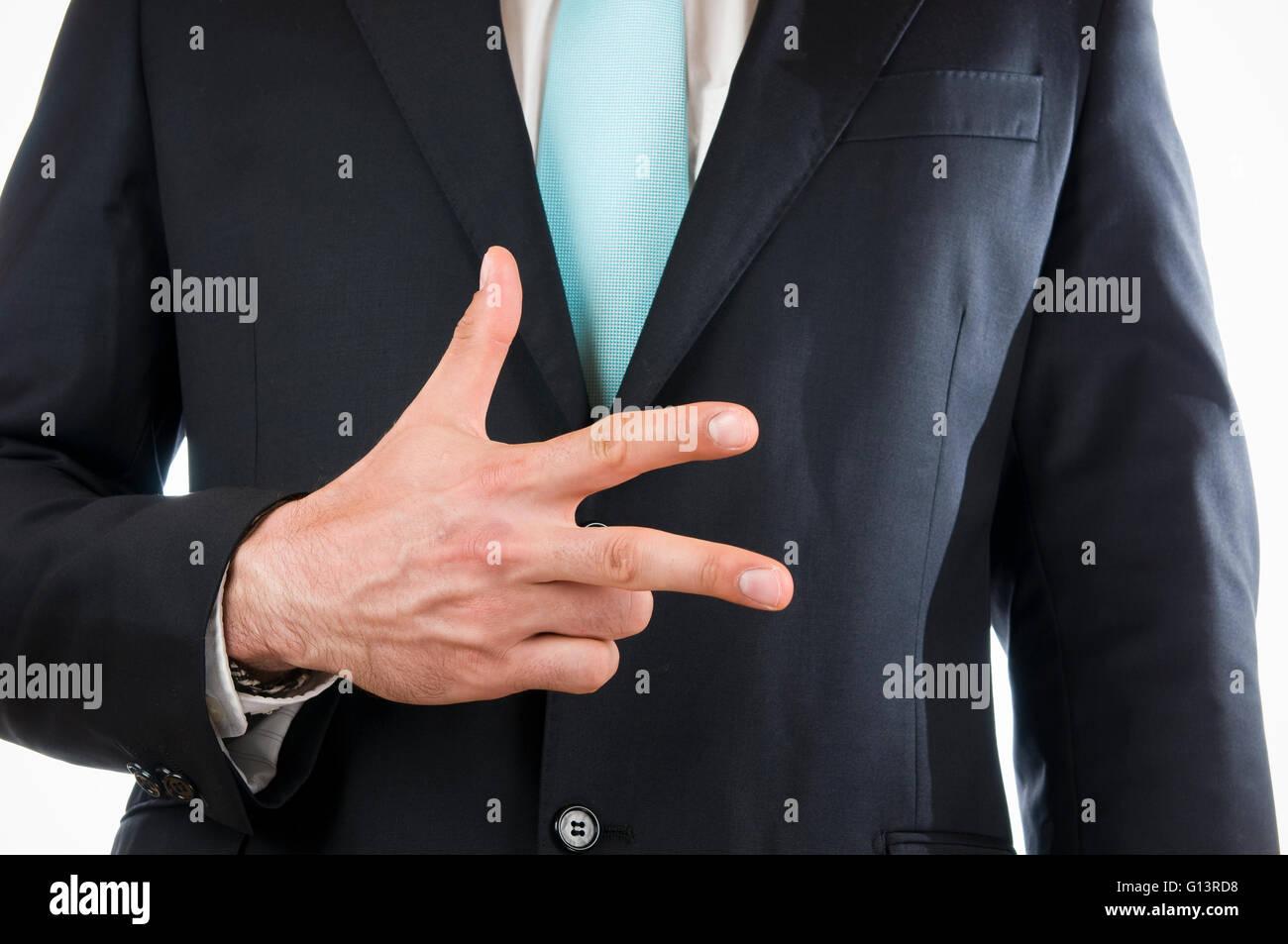 Vue ventrale d'un jeune homme en costume noir avec des mains à trois doigts pointant Photo Stock