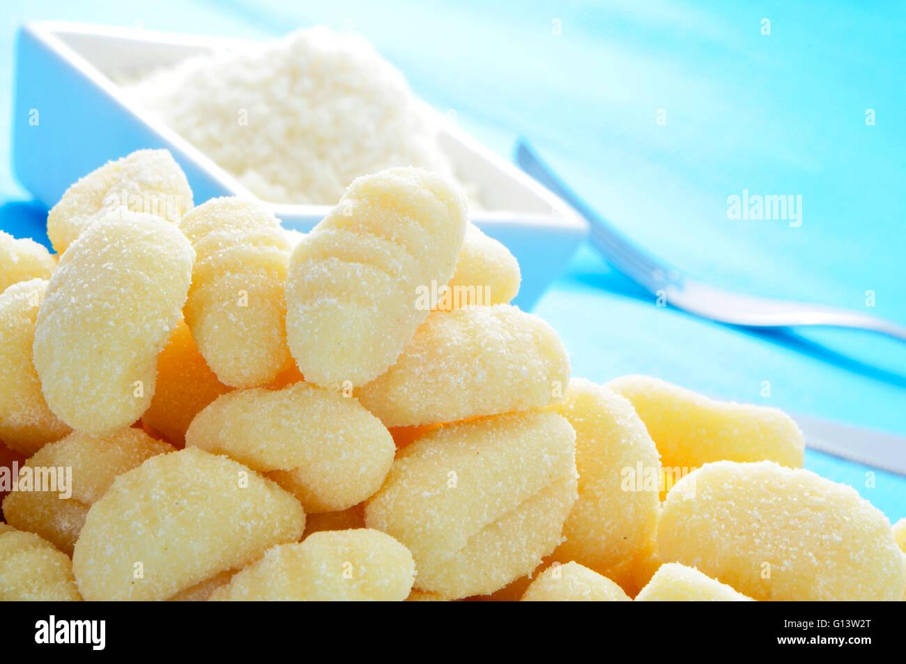 Libre d'un tas de gnocchi et un bol de fromage parmesan râpé sur une table Photo Stock