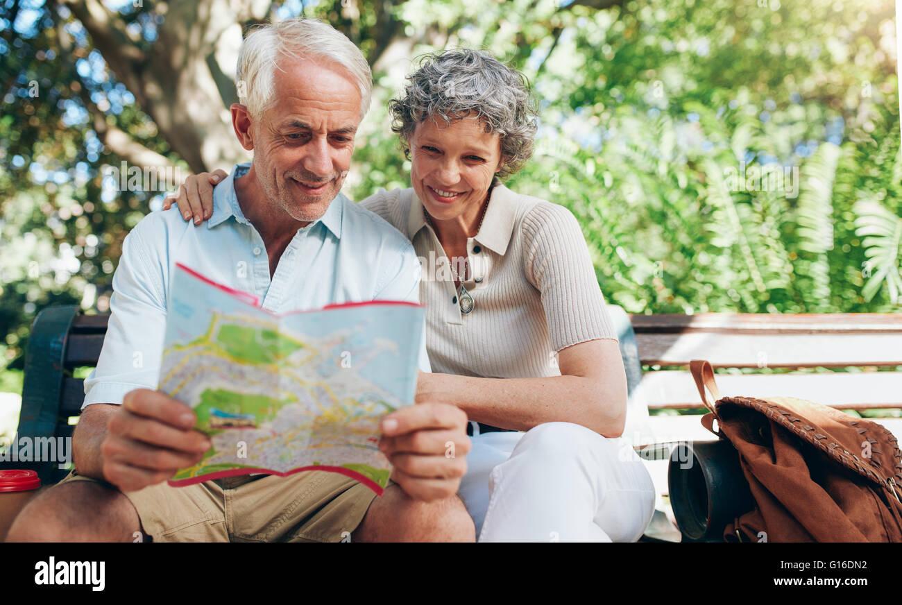 Couple à l'aide de plan de ville de sens. Couple de retraités en vacances assis dehors sur un banc Photo Stock