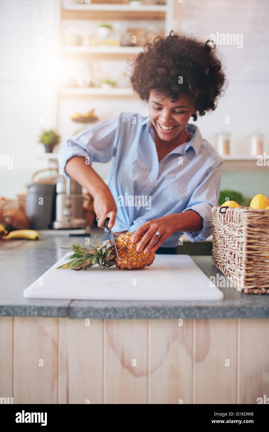 Jeune femme africaine debout derrière comptoir bar couper un ananas sur planche à découper. Femme Photo Stock